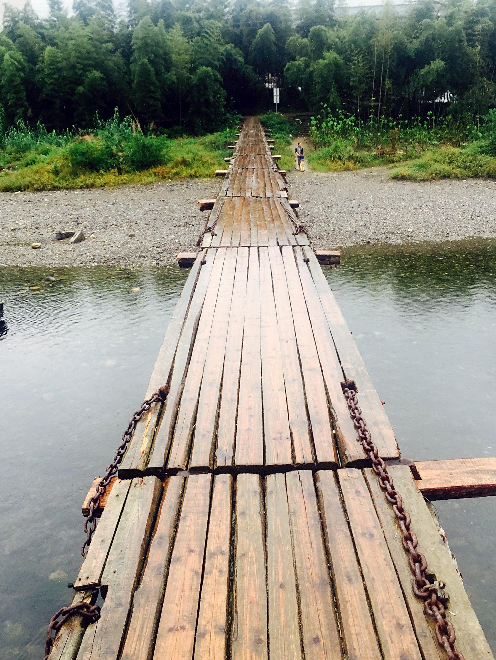 大家在桥上合影留念,走上去的时候,木板会颤悠悠地上下轻晃,让人想起