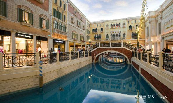 """<p class=""""inset-p"""" class=""""inset-p"""">澳门威尼斯人度假酒店,是澳门的著名景点,它集酒店、会展、购物、体育、综艺及休闲设施于一体的综合性场所,是来澳门游客的必游之地。</p><p class=""""inset-p"""" class=""""inset-p"""">酒店以水都威尼斯为主题,内部布满威尼斯特色拱桥、小运河及石板路,充满意式浪漫狂放的异国风情。这里有亚洲豪华的套房、大运河购物区、水疗中心。更拥有世界桌数量多的大厅。威尼斯人酒店的特点是没有标间,只有套房,每间套房的面积约70多平米,一晚的价格人民币1500元左右。即使你不选择这里入住,也可以来此血拼和游戏一把。</p><p class=""""inset-p"""" class=""""inset-p"""">澳门威尼斯人度假酒店极尽奢华,到处金碧辉煌,国际娱乐场分布在不同的楼层,每个娱乐场区都有很多游戏桌,娱乐场不能使用人民币,需在柜台处兑换筹码,小面值从几十元到200元不等,大面值可以到达惊人的200万元。其中玩法也有很多种,你都可以来过把瘾。</p><p class=""""inset-p"""" class=""""inset-p"""">如果你是购物狂,不能错过大运河购物中心。来一次贡多拉之旅,头顶一幅偌大的天幕,即使子夜时分,一样会出现蓝天白云,让人分不出是室内室外、昼夜晨昏。大运河的两岸云集了几百家大牌购物商铺,数十家的餐饮店,环境典雅瑰丽,仿如置身昔日威尼斯的街道。逛累了,也可在购物中心内的圣马可广场休息片刻,这里经常举行精彩的表演,如钢琴独奏、哑剧等。</p>"""