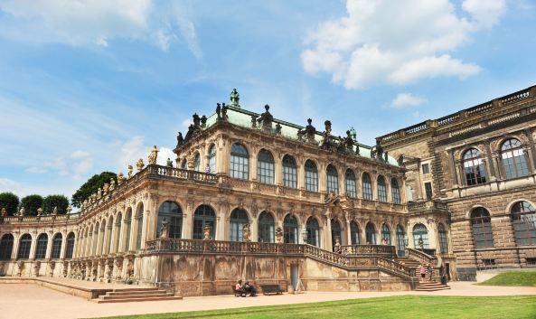 <p>德累斯顿王宫是德国最为恢弘、重要的宫殿建筑之一,1485年起便是历代撒克森王国统家族的居住地,也是当时该地区的政治权力中心。宫殿在二战中曾一度毁于战火,之后按照原貌复原重建。这座宫殿建筑融合了多种建筑艺术风格,鹅黄色的外墙配上红色屋顶和青铜色的圆顶,颇为雍容华贵。新建的封闭中庭的玻璃球形穹顶十分特别,这里设有售票处、纪念品商店、咖啡馆,免去游客以往须在露天排队等待的困扰。</p><p>这座巨大的宫殿现在以&ldquo;艺术科学宫&rdquo;的形式对外开放,共设有绿穹珍宝馆(Gr&uuml;nes&nbsp;Gew&ouml;lbe)、新绿穹珍宝馆(Neues&nbsp;Gr&uuml;nes&nbsp;Gew&ouml;lbe)、画廊(Kupferstich-Kabinett)、军械库(R&uuml;stkammer)和货币馆(M&uuml;nzkabinett)。此外,还有土耳其商会展览、艺术图书馆等场所也对公众开放。展品内容非常丰富,想一天全部看完比较困难,可以挑选自己感兴趣的展馆有重点的参观。</p><p>绿穹珍宝馆可谓是德累斯顿王宫的镇殿之宝,这个欧洲最大的珍宝馆内展出了上千件珍贵收藏品为保护文物,旧珍宝馆对每天的参观人数有所限,所以想要一睹这些传奇的欧洲珍宝的话最好提前预订门票。旧珍宝馆位于一层,展厅地面用黑白相间的大理石铺就,部分墙壁用天鹅绒装饰,十分华美。设有琥珀阁、象牙室、银器室、珍宝室、纹章室等不同主题的展厅。其中宝石厅的四面都配有镀金银镜,十分震撼。</p><p>2010年新设的新珍宝馆位于王宫二层,门票可直接在售票处购买。展厅内配备了防晕眩玻璃和最先进的照明技术,便于更好地呈现展品的每一个细节。这里主要珍藏了印度莫卧儿王朝时期的珠宝,包括4909颗钻石,红宝石160,164绿宝石、蓝宝石、珍珠等,璀璨夺目。其中一颗雕有185张人脸的樱桃核和用象牙雕制而成的护卫舰(Fregatte,&nbsp;Sign)不可错过。</p><p>如果你是绘画爱好者,可以去画廊看一看,这里收藏有图卢兹&nbsp;-&nbsp;劳特累克,毕加索、巴塞利兹、丢勒,凡艾克,伦勃朗,米开朗基罗,弗拉戈纳尔和卡斯帕&middot;大卫&middot;弗里德里希等著名艺术家的版画、素描等作品。如果觉得光是远远参观不过瘾,可以去位于王宫三层的学习室近距离欣赏名画。</p><p>王宫大厅现用作军械库展览,在这里,你不仅可以看到欧洲本土的格式兵器、装备,也可以欣赏到中东风情的战时装备。展出的10,000武器包括盔甲,头盔,盾牌,剑,剑杆、匕首、军刀、狼牙棒手枪、步枪等等。</p><p>与军械库毗邻的货币馆则通过一枚枚小小的货币和纪念章展现了德累斯顿的历史文化,同时展出的铸币机器也很有意思。</p><p>除了宫殿内的各式展品外,位于北侧靠Augustus路的外墙面上的壁画也是不容错过,在这座长达102公尺的墙上,以磁砖镶嵌画的方式绘有一高8米长的绵长壁画&mdash;&mdash;《君主的行列》(Der&nbsp;Furstenzug),图中的人物即撒克森历代君王的骑马像;使用的磁砖多达2万7000多块,始造于19世纪末、完成于20世纪初,是整座王宫在二次大战幸存下来的少数原物之一。</p>
